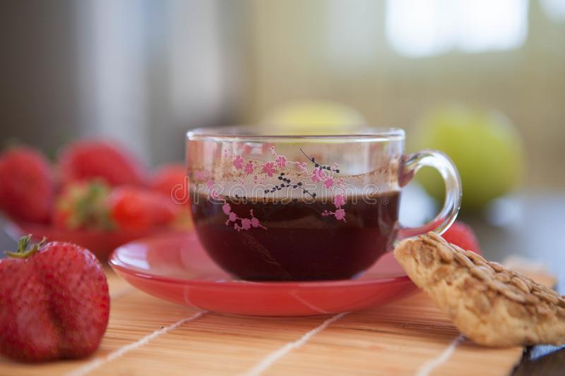 A cup of beautiful black English tea for breakfast with strawberries and cookies. royalty free stock images