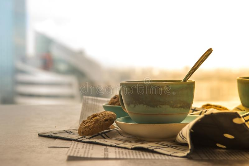 Cup of black coffe with spoon on supported dish on fabric on black and white newspaper is put on hard table in the early morning royalty free stock photos