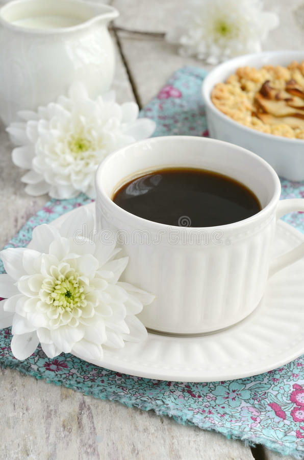Cup of black coffee and apple tart. Breakfast with cup of black coffee, apple tart and white flowers royalty free stock images