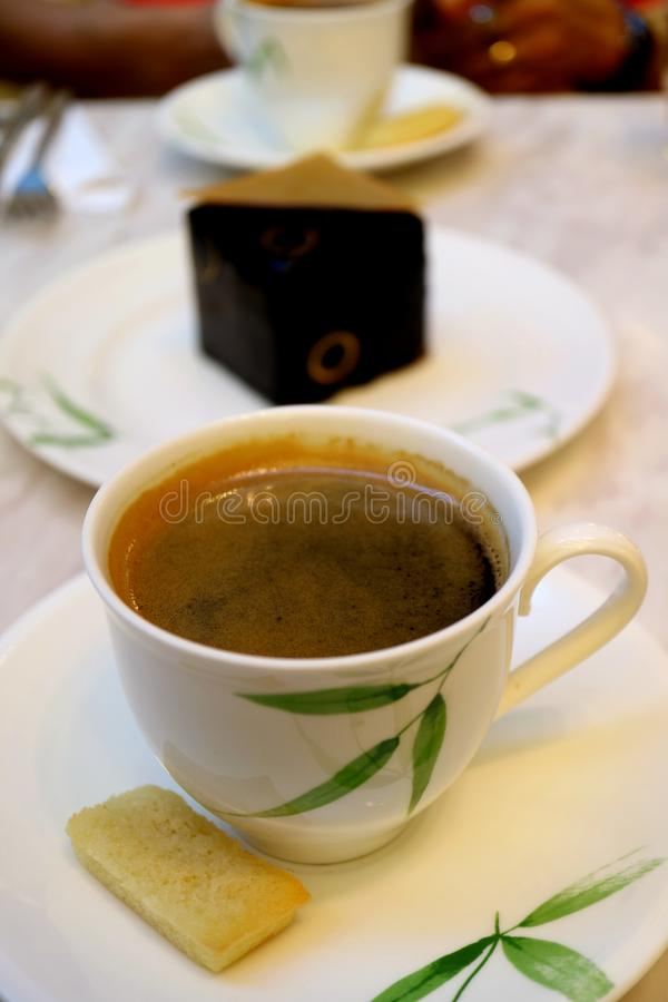 Cup of black coffee with blurry dark chocolate cake and another coffee cup in background royalty free stock photography