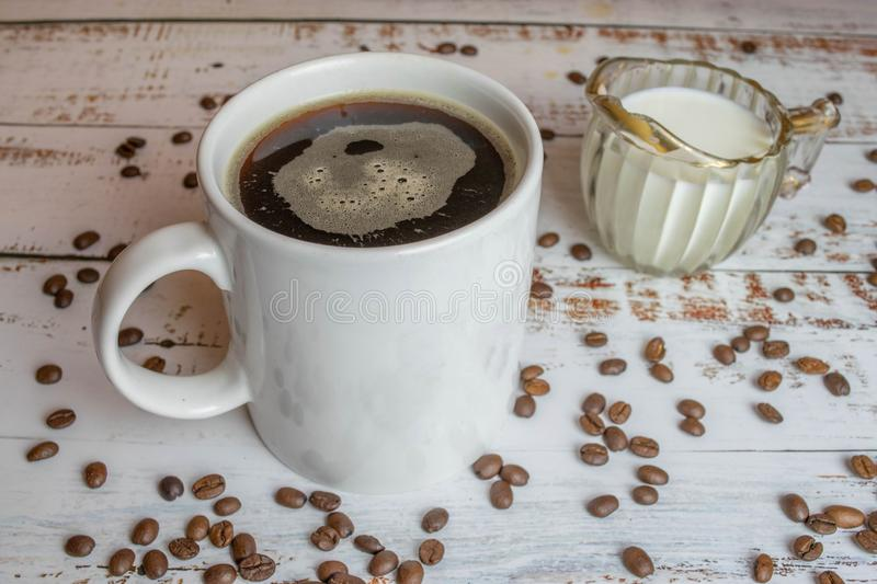 Cup with black coffee and bowl with milk on white wooden table with organic coffee grains. Cup with black coffee and bowl with milk on white wooden table with stock photo