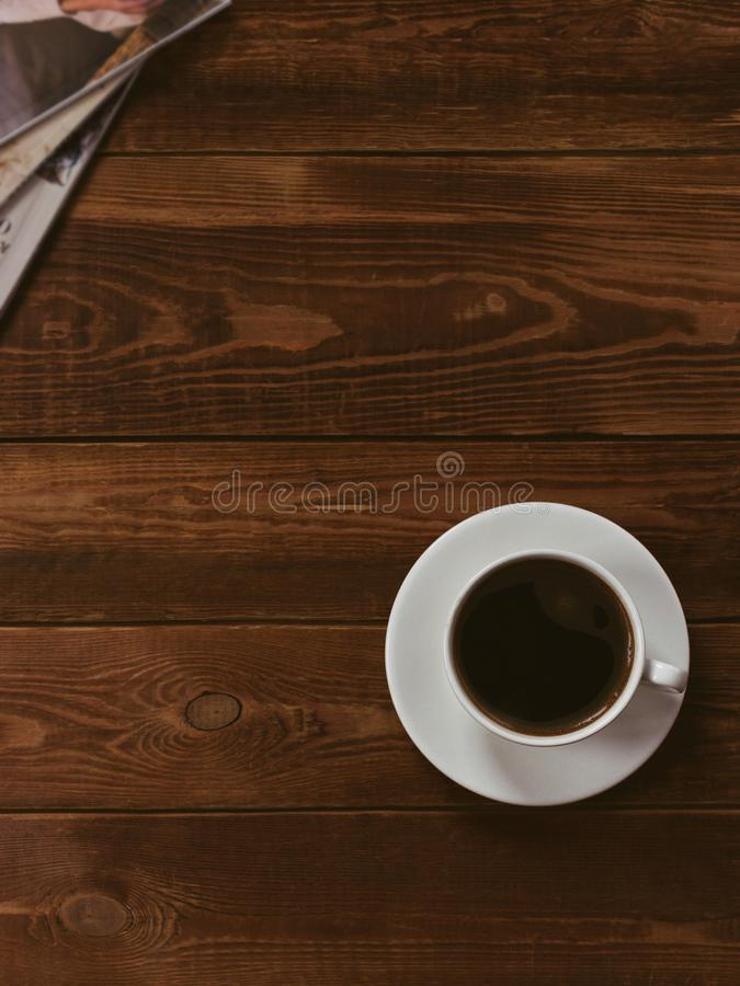 Cup of black coffee on a brown wooden table with fashion magazine. Author processing, film effect, low key. stock photos