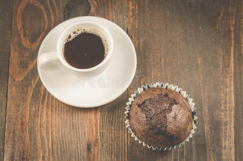 Cup of black coffee and a chocolate muffin/cup of black coffee and a chocolate muffin on a dark wooden background. Top view. Cup of black coffee and a chocolate stock photo