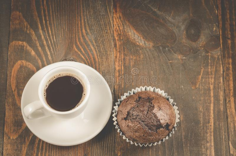 Cup of black coffee and a chocolate muffin/cup of black coffee and a chocolate muffin on a dark wooden table. Top view and stock photos