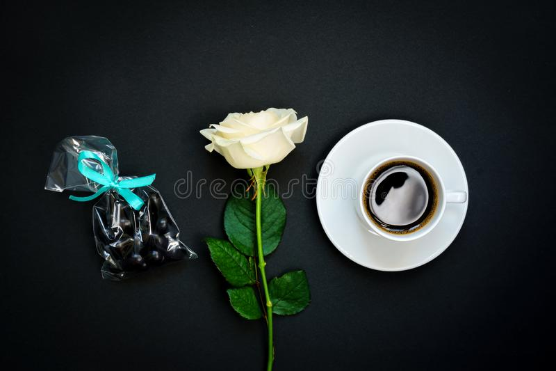 Cup of black coffee, chocolate sweets and white rose on black background, Top view, copy space. Toned image royalty free stock image