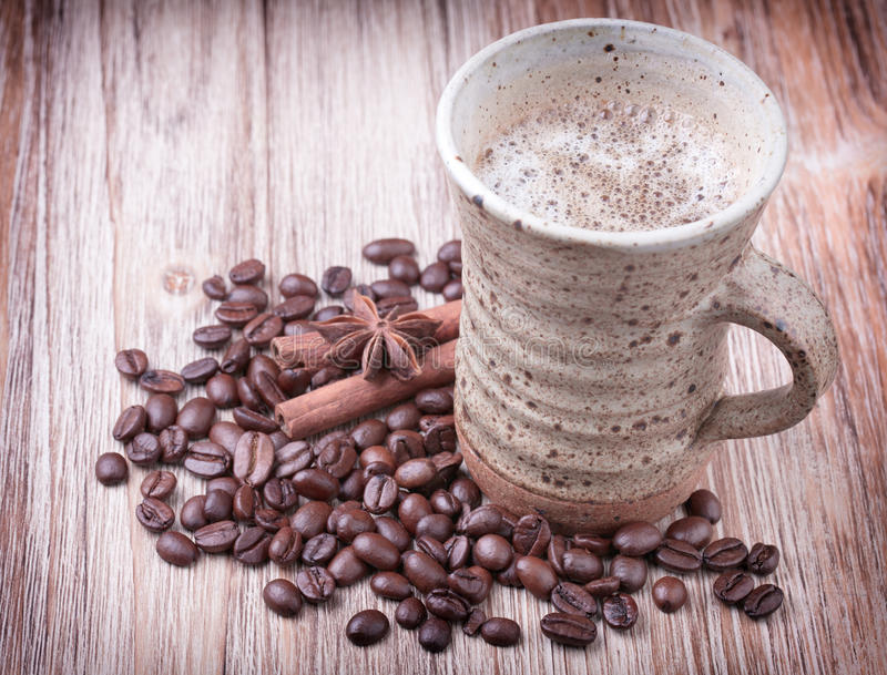 Cup of black coffee, cinnamon, aniseed and roasted coffee beans royalty free stock image