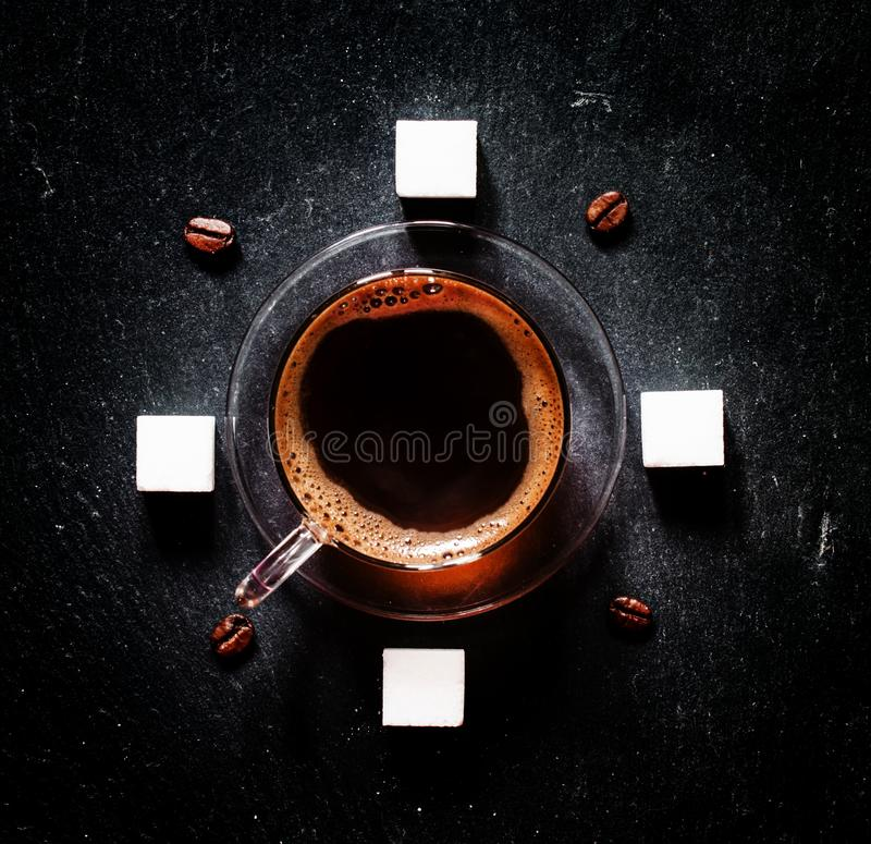 Cup of black coffee, coffee beans, white refined sugar, dark background, top view royalty free stock photo