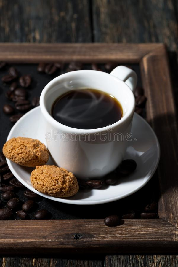 Cup of black coffee and cookies on a tray, vertical closeup. Cup of black coffee and cookies on a tray, closeup royalty free stock photography