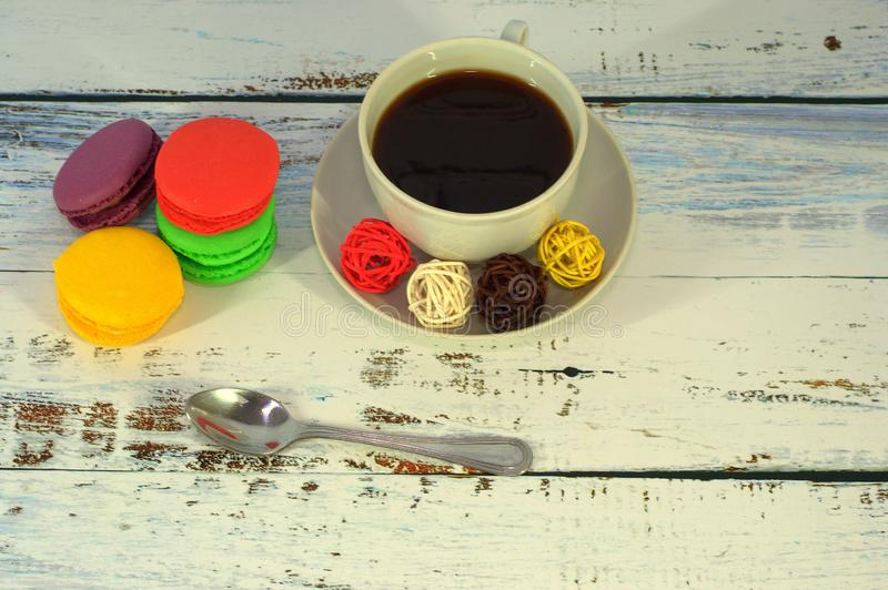 A cup of black coffee with decorative balls on a saucer and a group of four multi-colored macaroons. Clos-up stock image