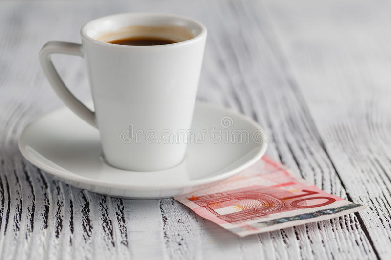 Cup of black coffee and euro banknotes stock image
