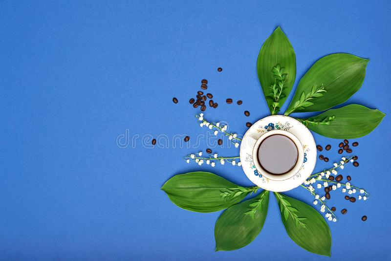 Cup of black coffee with flowers on blue coloured art background. Good Morning coffee floral setup. royalty free stock images