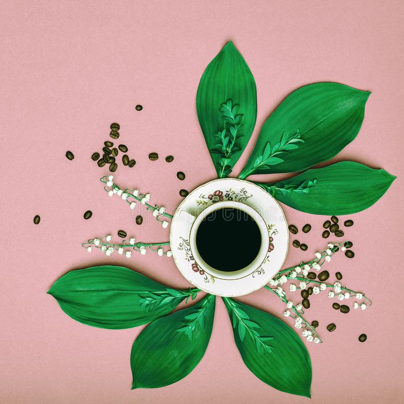 Cup of black coffee with flowers on pink coloured art background. Good Morning coffee. Cup of black coffee with flowers on pink coloured art background. Good royalty free stock photography