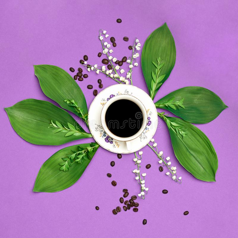 Cup of black coffee with flowers on purple coloured art background. Good Morning coffee floral setup. Cup of black coffee with flowers on purple coloured art stock photo