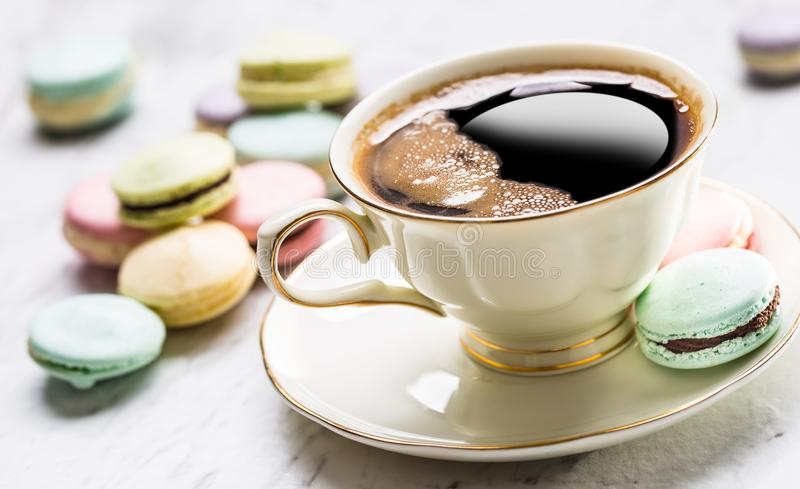 Cup of black coffee with french macaroons stock photo