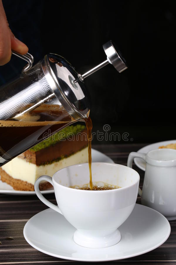 Cup of black coffee and french press. A back lit image of coffee being poured into small coffee mugs from a French Press with the light source being a window royalty free stock photo