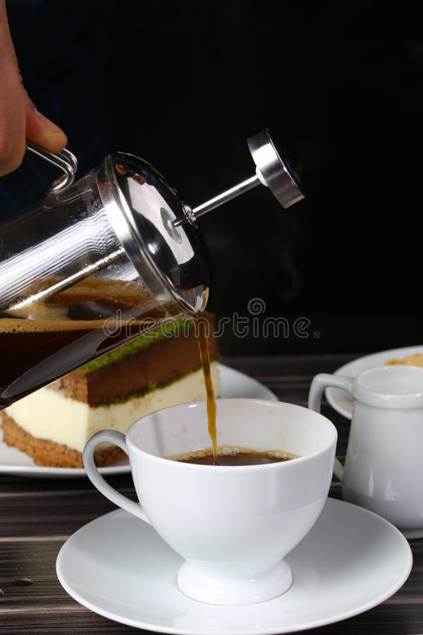 Cup of black coffee and french press. A back lit image of coffee being poured into small coffee mugs from a French Press with the light source being a window royalty free stock photography