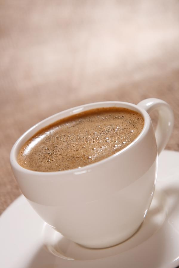 Cup of black coffee with froth on brown background royalty free stock photography