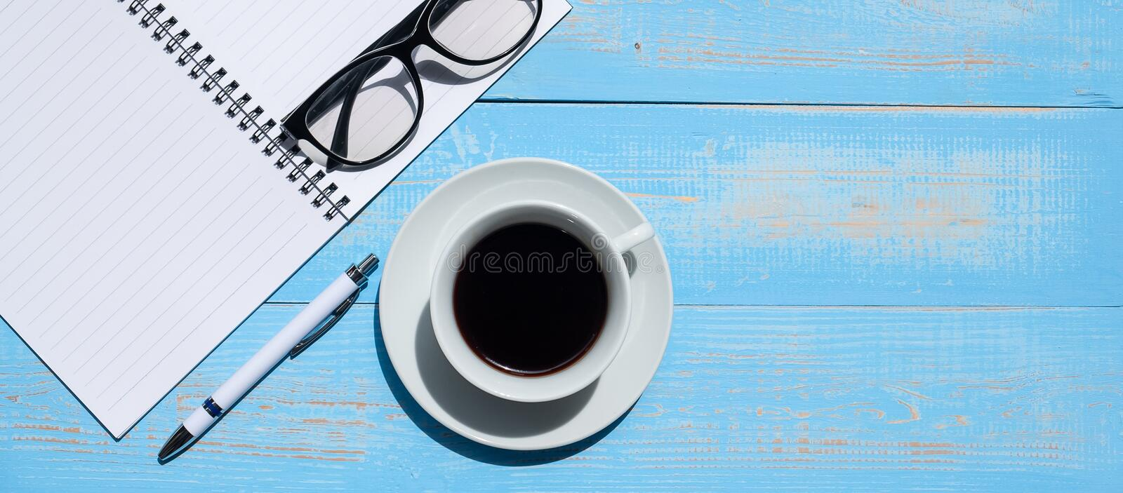 Cup of black coffee and smart phone with office supplies; pen, notebook and eyes glasses on blue wooden table background. Cup of black coffee with office stock images