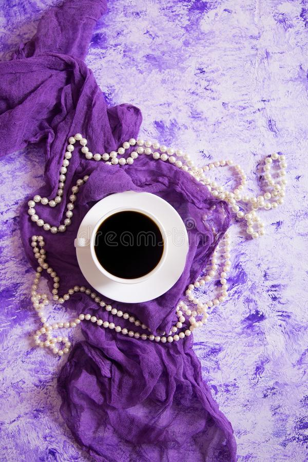 Cup of black coffee on purple tender fabric surrounded with white pearl necklace on marble table. Top view stock image