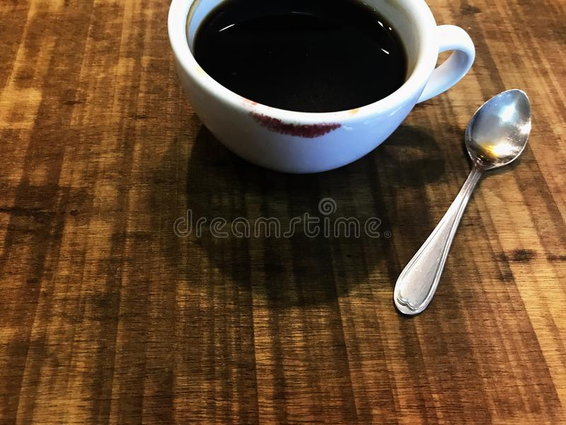 Cup of black coffee with red lipstick mark and silver spoon. Cropped shot of white cup of black coffee with red lipstick mark and silver spoon on natural brown stock photo