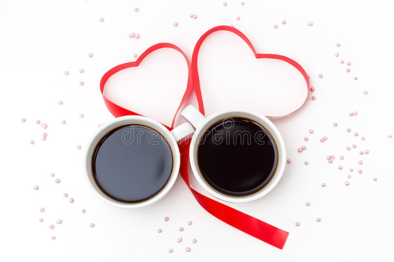 Cup of black coffee and a red ribbon in the shape of hearts on a white background with pink sprinkles. Top view, romantic love background for Valentine`s day royalty free stock photos
