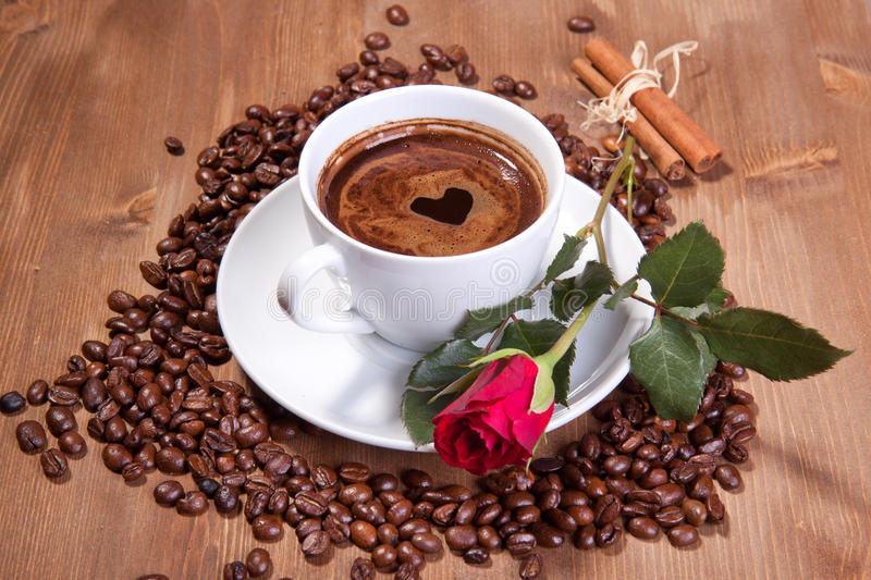 Cup of black coffee and red rose. White cup of black coffee with coffee beans and red rose royalty free stock image