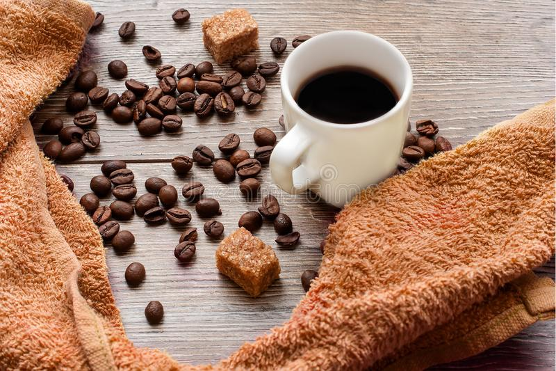 Cup of black coffee, roasted coffee beans with pieces of cane sugar on wooden table. Top view stock photos
