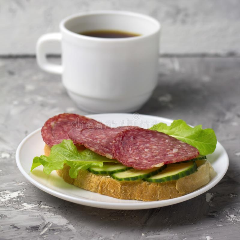Cup of black coffee and sandwich. With sausage, cucumber and salad square image royalty free stock photography