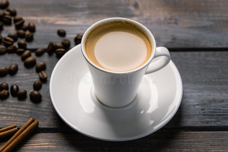 Cup of black coffee on a saucer with cinnamon on a dark wooden table. Coffee beans scattered on the table stock photo