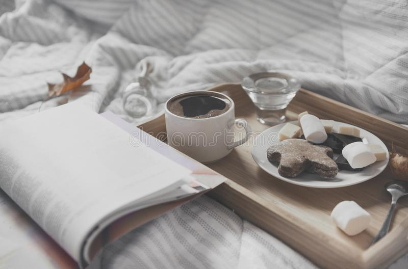 Cup of black coffee, saucer with cookies, marshmallows, chocolate pieces on a tray on a white plaid, open magazine, maple dry royalty free stock photos
