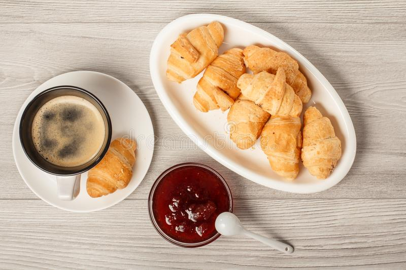 Cup of black coffee with saucer, fresh croissants on white porcelain dish, strawberry jam in bowls stock image