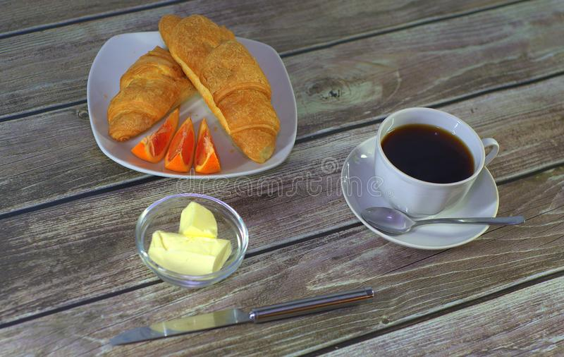 A cup of black coffee on a saucer with a spoon, a plate with croissants and lemon slices with butter stand on a wooden table. stock photography