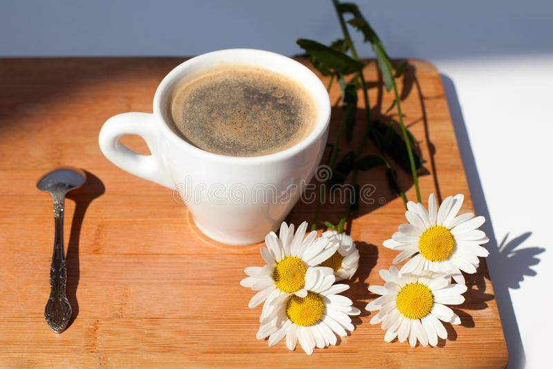 A cup of black coffee, silver spoon, branch of white daisy flowers on wooden background top view. A cup of black coffee, silver spoon and branch of white daisy stock image