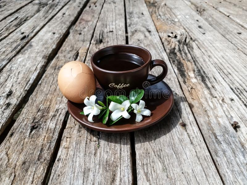 Cup of black coffee. With soft-boiled egg and white flowers on the wooden table royalty free stock photo