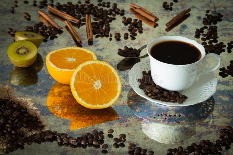 A cup of black coffee with spilled coffee beans, pieces of orange, sticks of cinnamon and kiwi.  Photo in vintage style stock photo