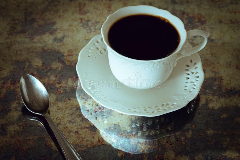 A cup of black coffee with a spoon in vintage style royalty free stock photography
