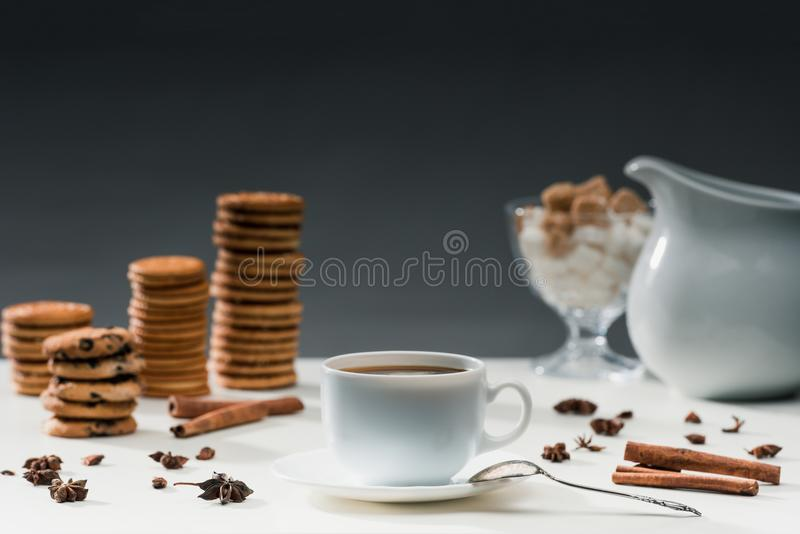 Cup of black coffee on table with cookies. And spices stock photos