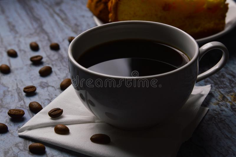 A cup of black coffee on table with sponge cake. And coffee beans royalty free stock photos