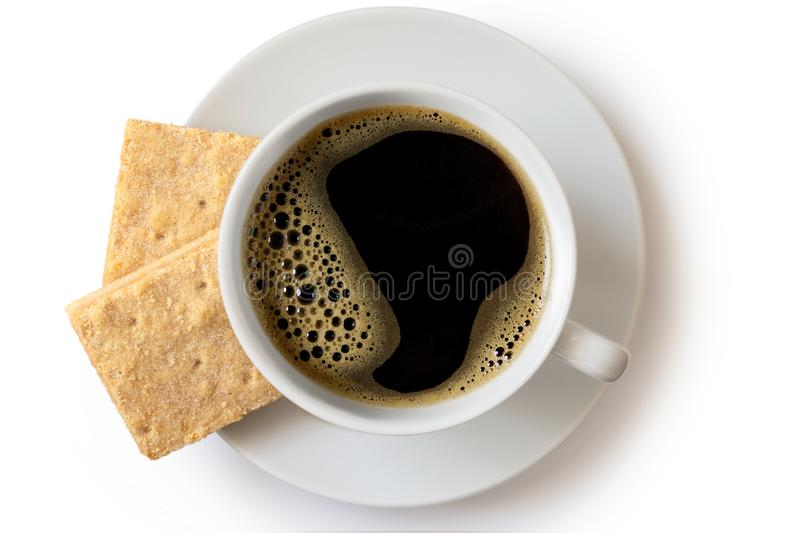 A cup of black coffee with two square shortbread biscuits isolated on white from above. White ceramic cup and saucer. stock image