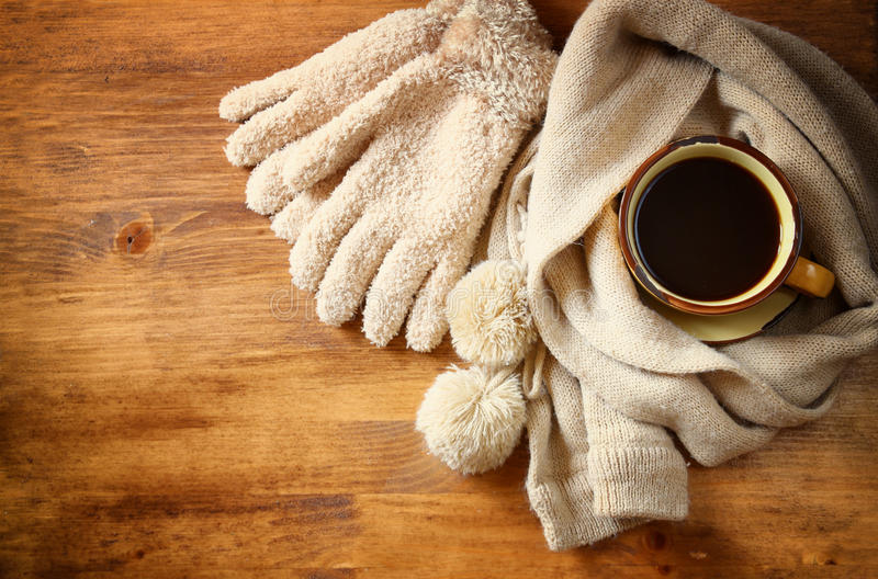 Cup of black coffee with a warm scarf on wooden background. filreted image royalty free stock image