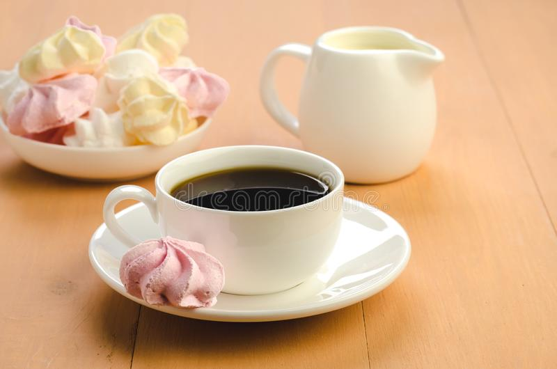 cup of black coffee in a white cup/white cup with black coffee and meringue cookies royalty free stock images