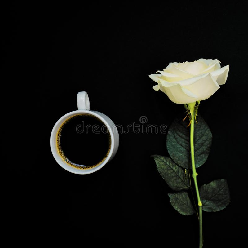 Cup of black coffee and white rose on black background, Top view, copy space. Toned image.  royalty free stock photo