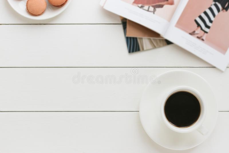 Cup of black coffee on a white wooden table with fashion magazine. Author processing, film effect. royalty free stock images