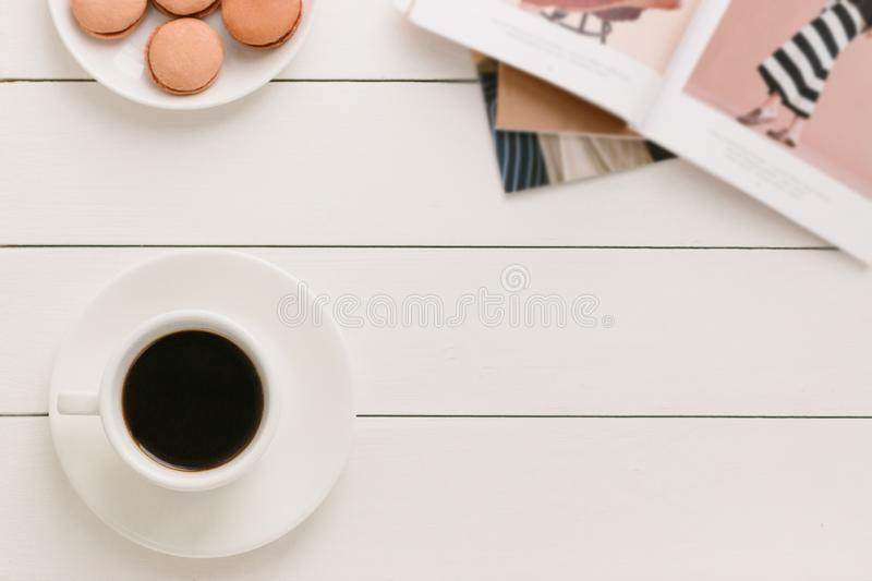 Cup of black coffee on a white wooden table with fashion magazine and macaroons. Author processing, film effect. royalty free stock photography