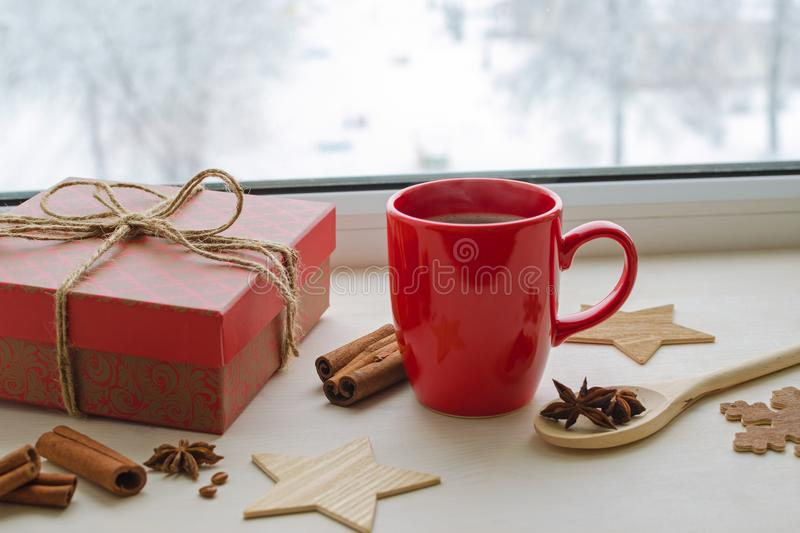 Cup of black coffee on a winter window sill. Red cup with black coffee on winter window sill, gift in beautiful box, anise stars, cinnamon sticks, wooden royalty free stock photos