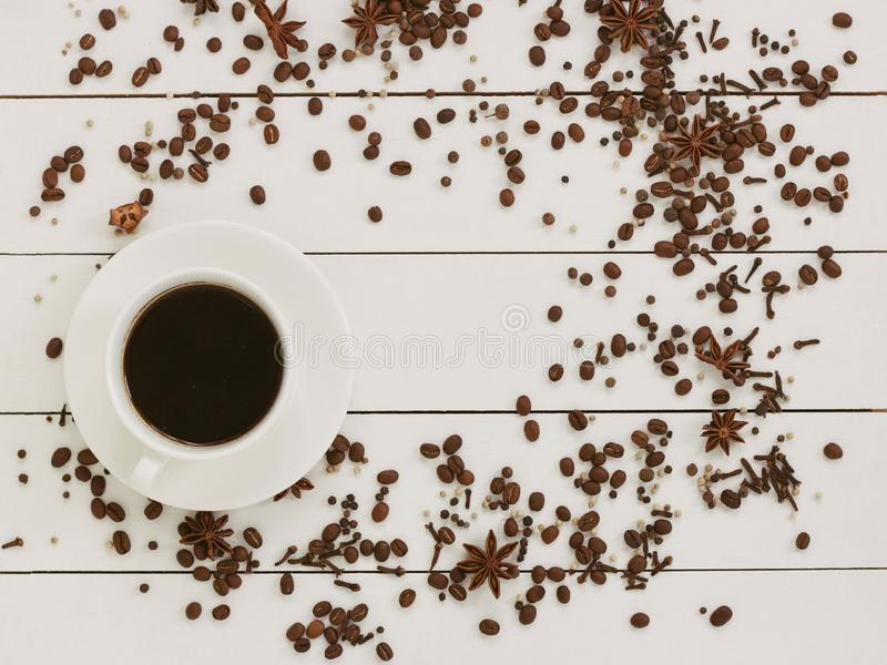Cup of black coffee on a wooden background with spices and coffee grains. Author processing, film effect. royalty free stock image