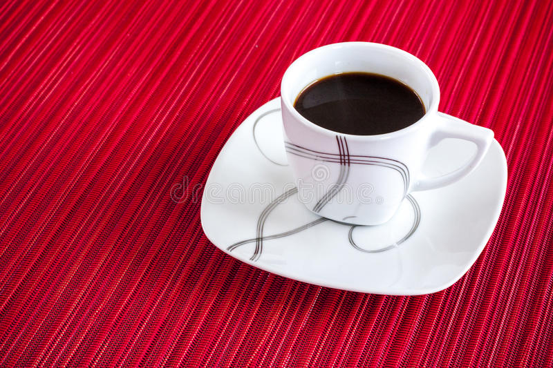 Cup Black Expresso. An elegant cup of expresso with a red tablecloth stock photography