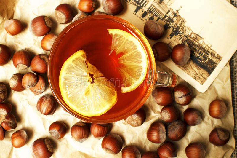 A cup of black hot tea with lemon, hazelnut on a beige paper with a retro card stock photos