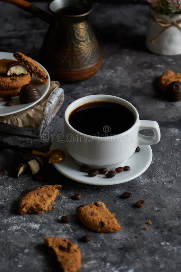 Cup of black strong coffee with coffee beans and cookies on dark background royalty free stock photos