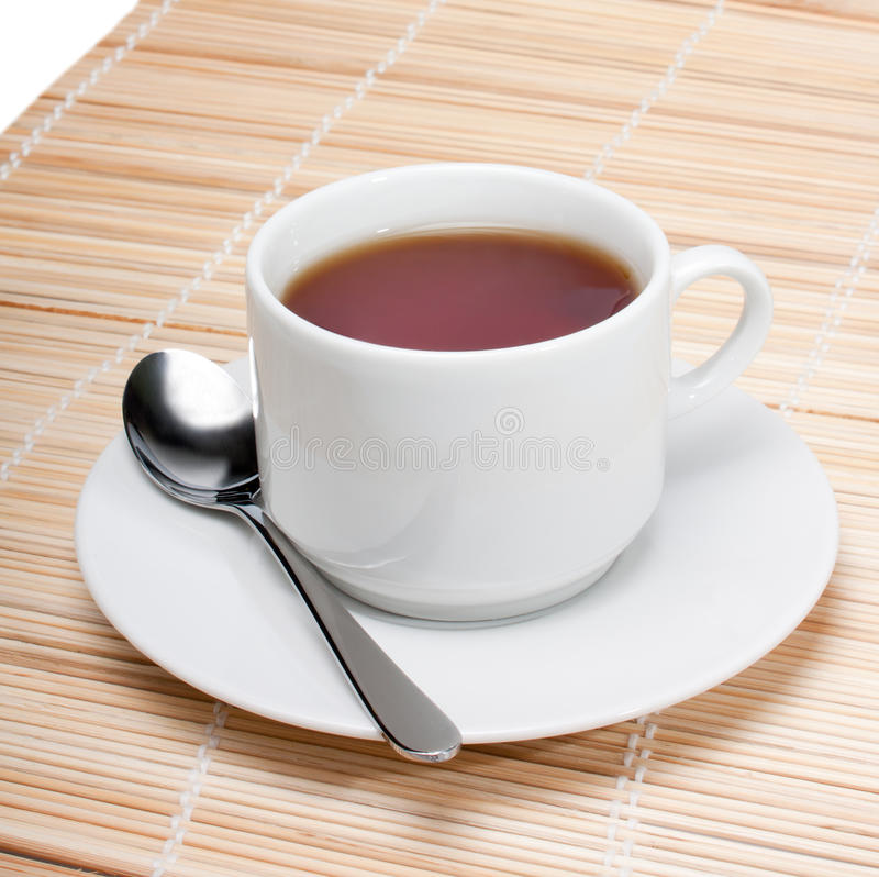 Cup of black tea. With spoon on napkin isolated over white background stock images
